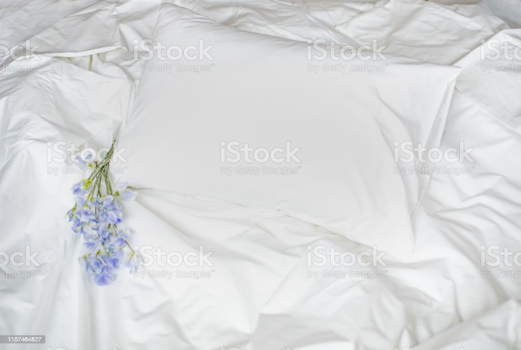 Flowers on the messy bed, white bedding items and blue flowers...