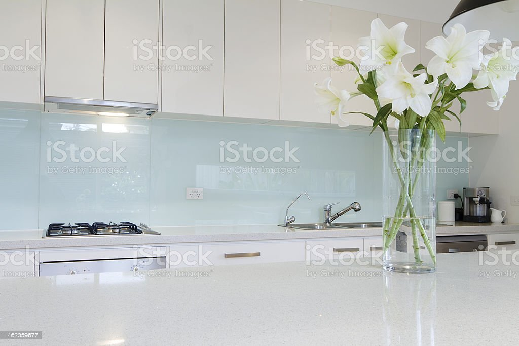 Flowers on white kitchen bench stock photo