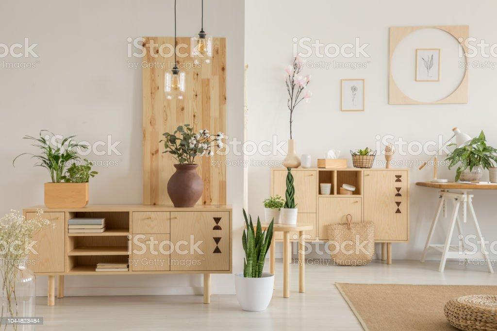 Bloemen op de houten kast in natuurlijke woonkamer interieur met