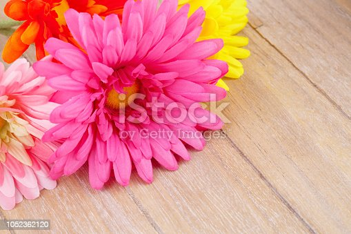 Colorful fabric daisies on wooden background, closeup picture.
