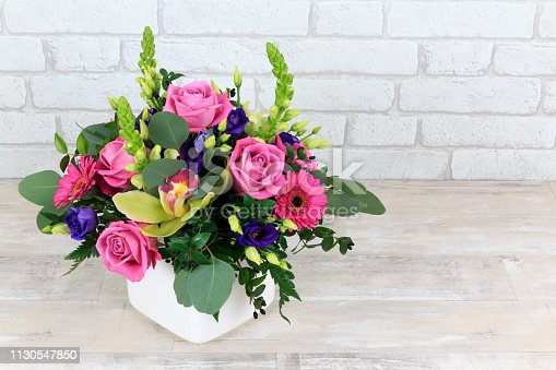 Mixed pink floral arrangement in a white pot on shabby worktop with white brick background