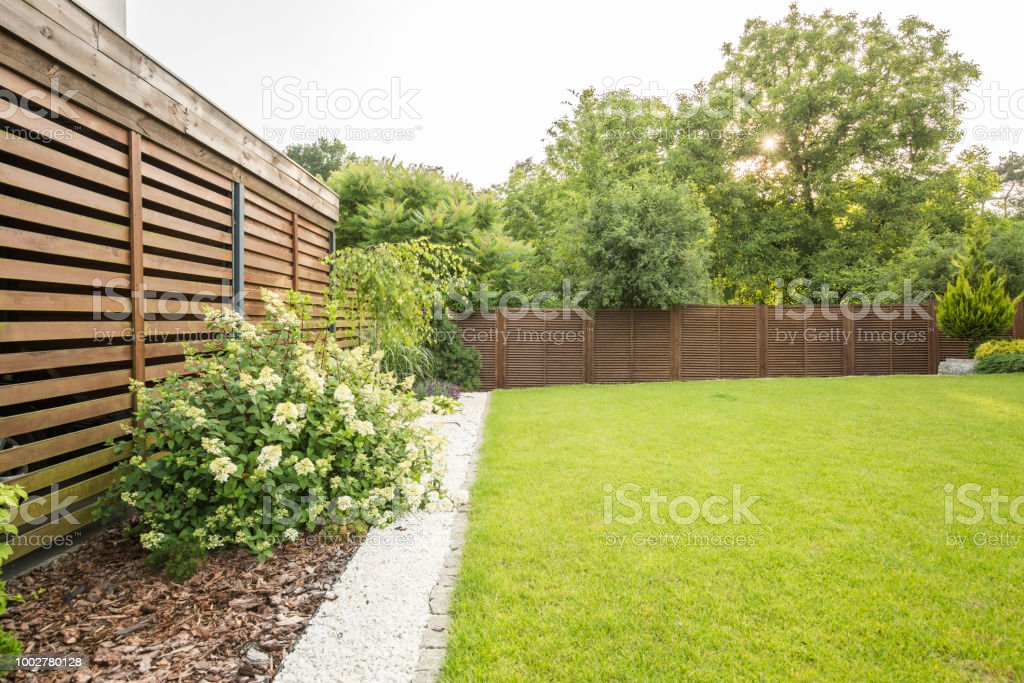 Flowers, trees and green grass in the garden of house with wooden screen. Real photo stock photo