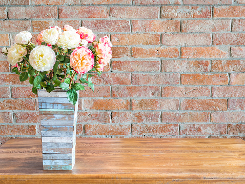 Flowers vase on wooden table top with brick wall background