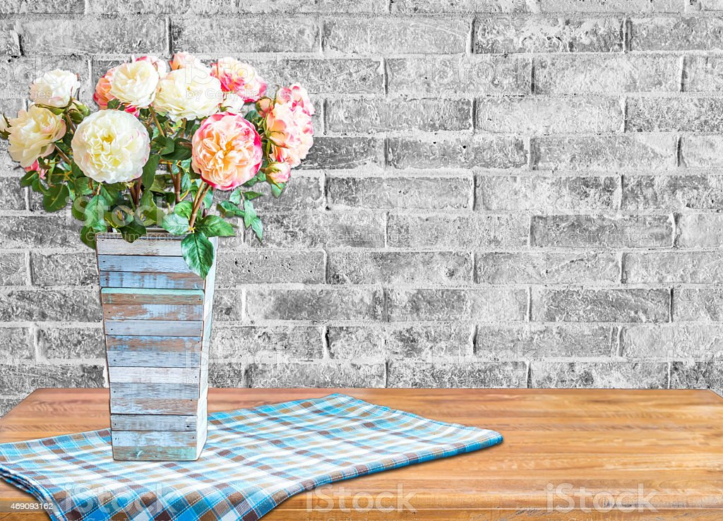 Flowers vase on wooden table top with brick wall background stock photo