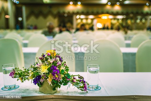 1047189958 istock photo Flowers with drink water on table, Meeting room defocus with flowers 1166261932