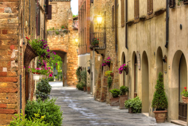 Flowery streets on a spring day in a old village Pienza Flowery streets on a spring day in a small old village Pienza, Tuscany. pienza stock pictures, royalty-free photos & images