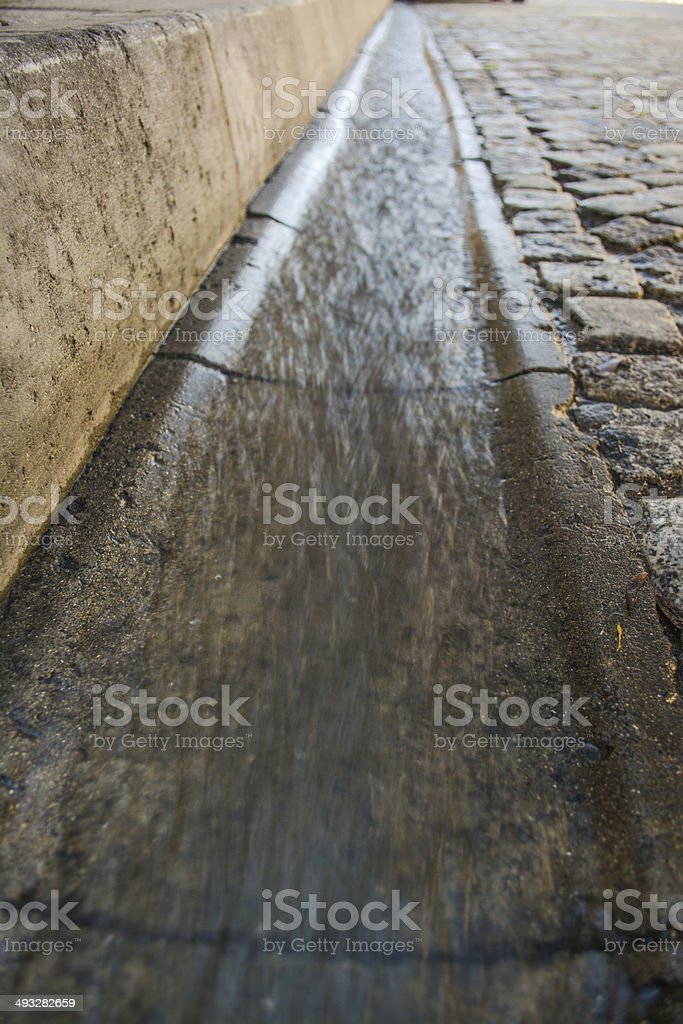 Flowing rain water near the road stock photo