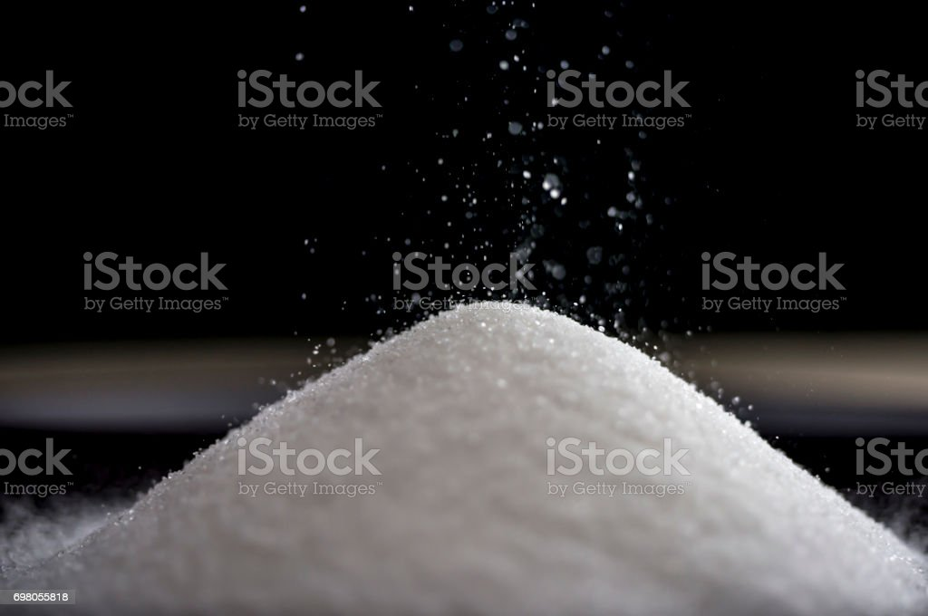 Flowing sugar forming a pile as it falls stock photo