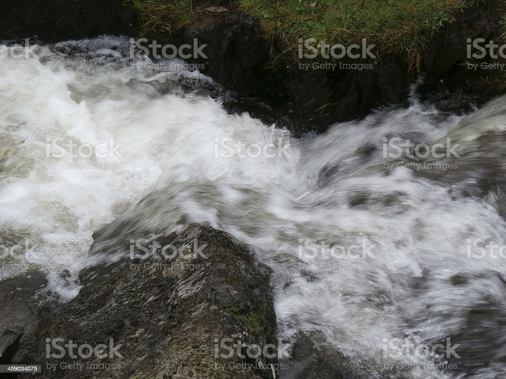 Flowing water over rocks stock photo