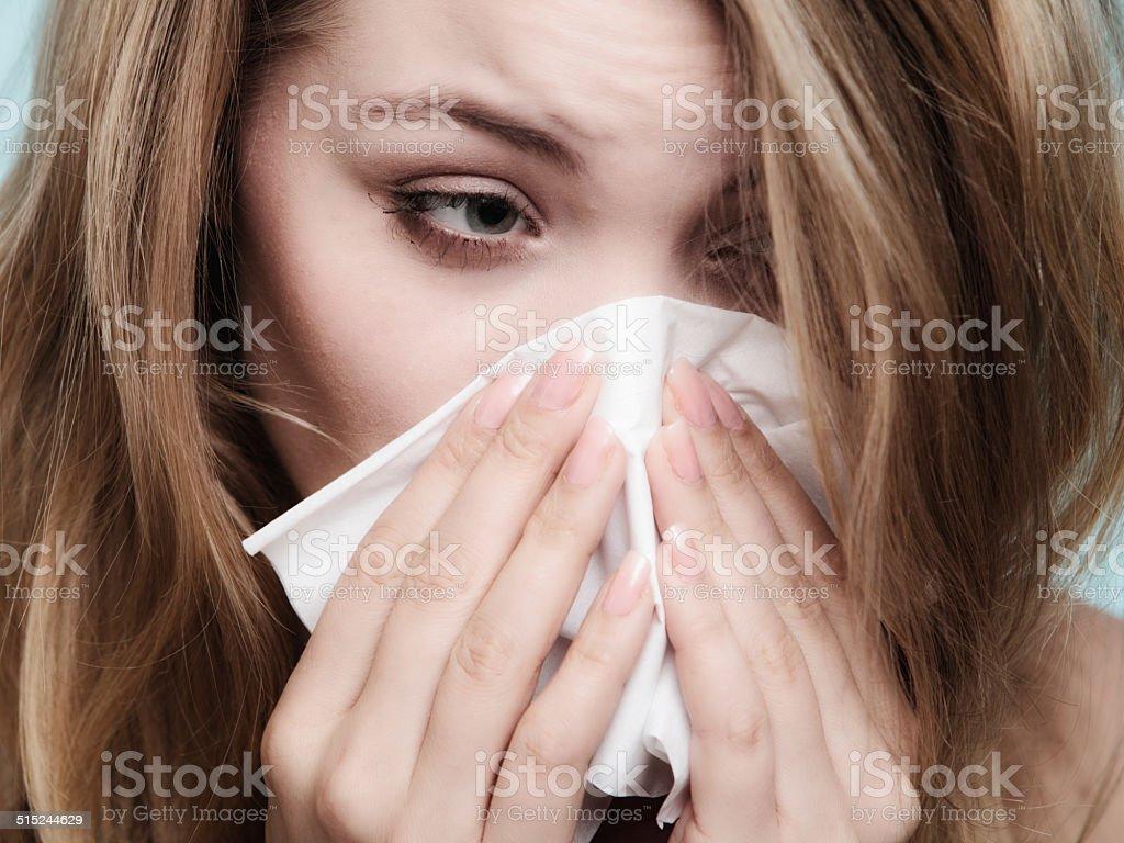 Flu allergy. Sick girl sneezing in tissue. Health stock photo