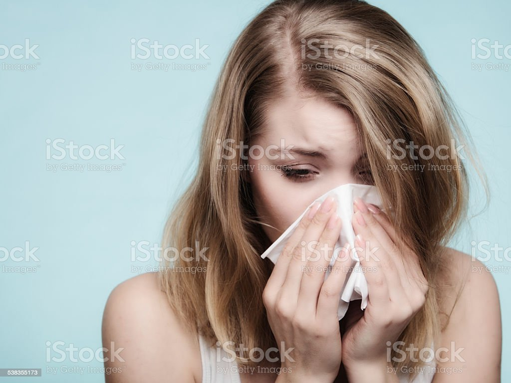 Flu cold or allergy symptom. Sick woman girl sneezing in tissue on...