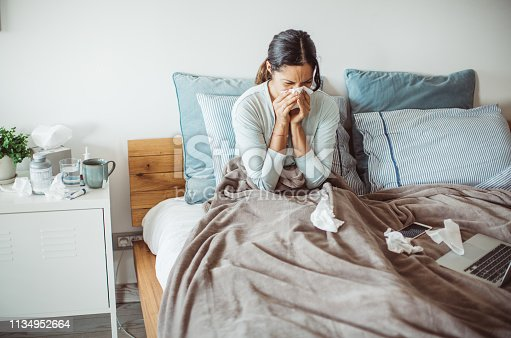 Woman with flu in bed, she use home medicine to handle sickness