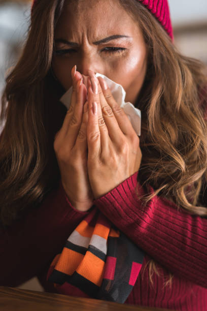 Flu cold or allergy symptom.Sick young woman  sneezing in tissue, allergies, headaches. Flu cold or allergy symptom.Sick young woman  sneezing in tissue, allergies, headaches. respiratory disease stock pictures, royalty-free photos & images