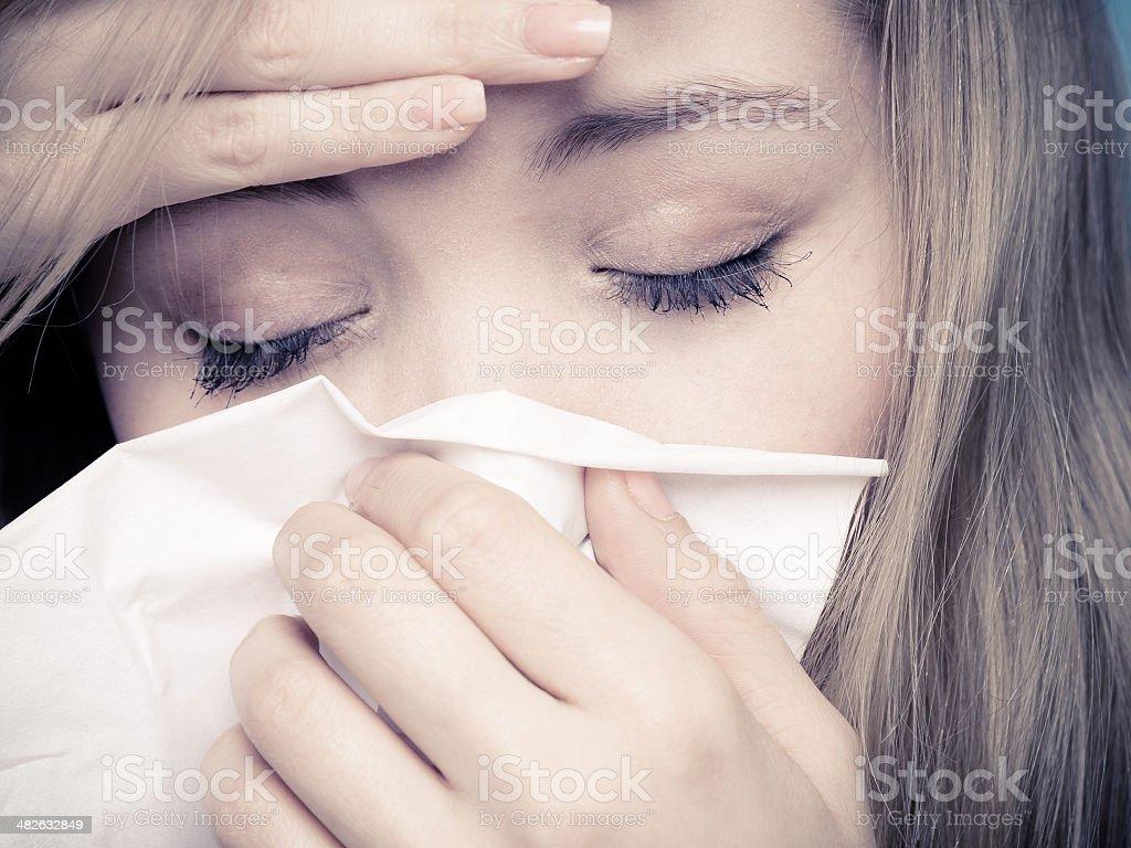 Flu fever. Sick girl sneezing in tissue. Health stock photo