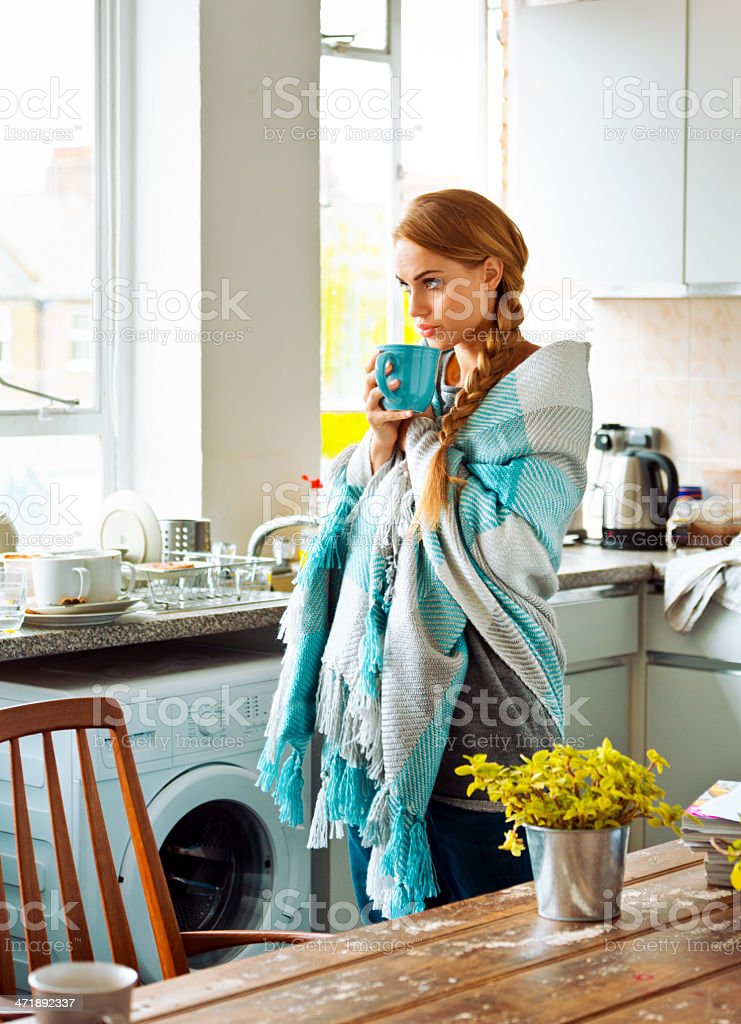 Flu Young woman has a cold, standing in a kitchen wrapped in blanket, holding a tea cup and looking through window. 20-24 Years Stock Photo