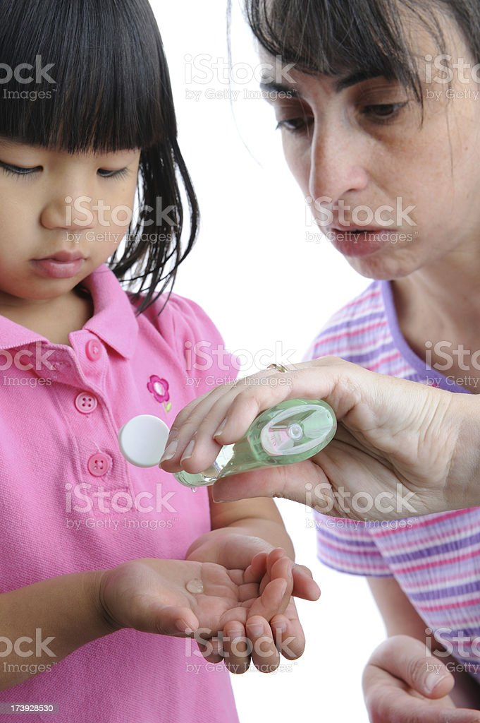 Flu Prevention: Woman Applying Sanitizing Gel to Child's Hands stock photo