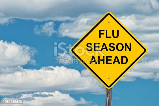 Flu Season Ahead Caution Sign With Blue Sky Background