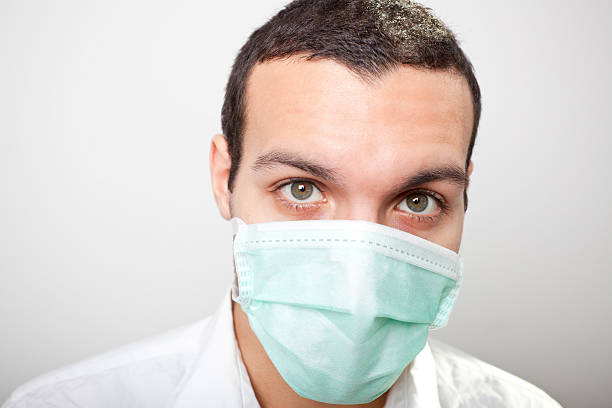 Flu Season Caucasian young man wearing a protective face mask as protection against the flu virus and the common cold.Similar Images: human parainfluenza virus stock pictures, royalty-free photos & images