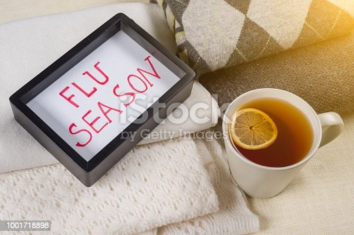 Flu season text in frame. Background warm woolen clothes, cup of hot tea.