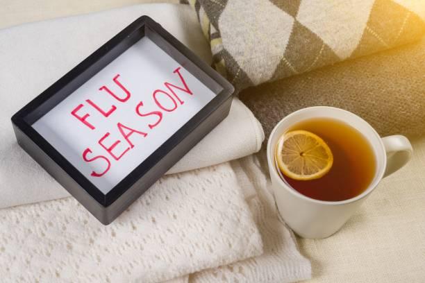 grippe-saison-text im rahmen. hintergrund warme wollene kleidung, tasse heißen tee. - erkältung und grippe stock-fotos und bilder