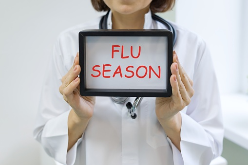 Flu season text in the hands of a female doctor.