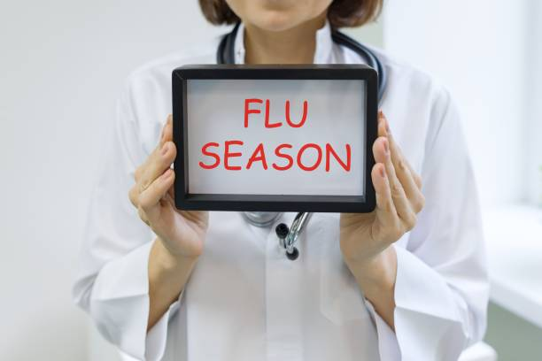 Flu season text in the hands of a female doctor stock photo