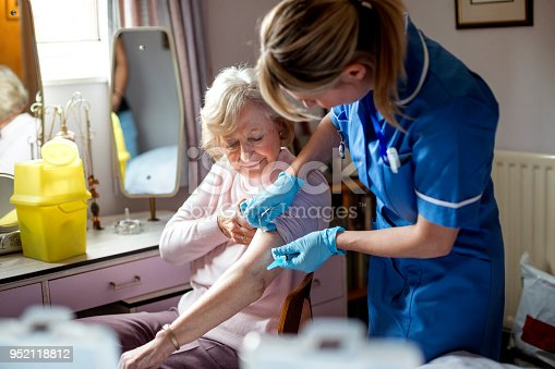 A nurse visits an elderly woman in her home. The elderly woman is happily sitting on a chair at her dressing table.