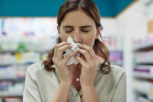 Shot of a young woman sneezing in a pharmacy