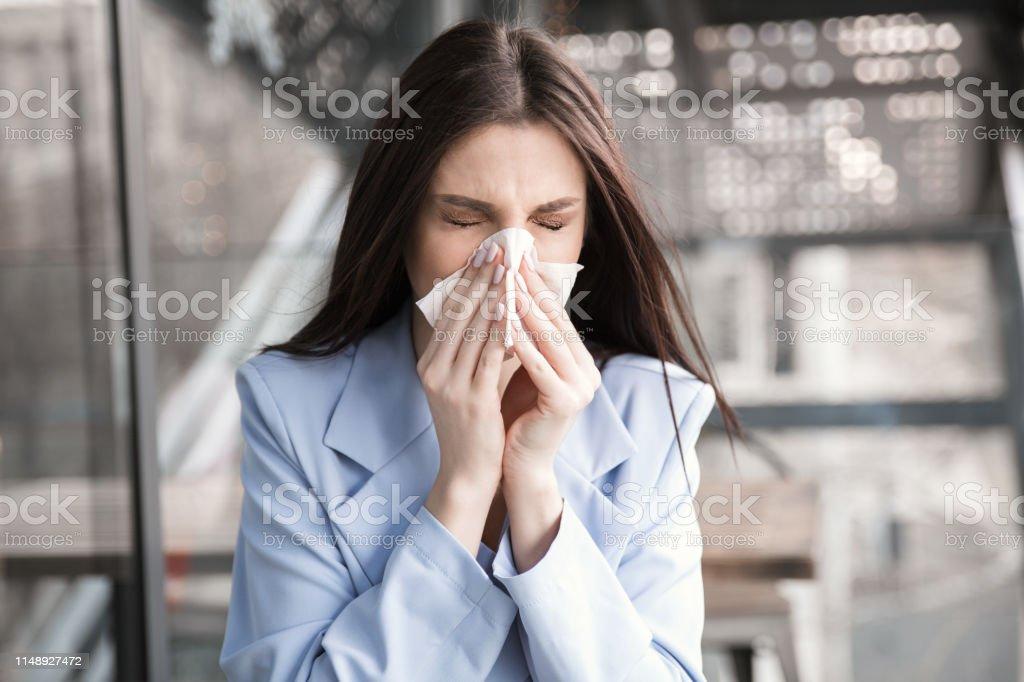 Flu. Young woman got nose allergy, flu sneezing nose. Closeup...