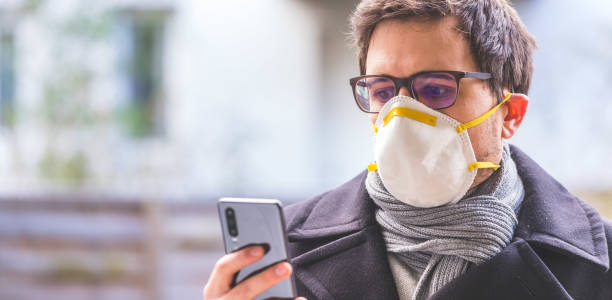 flue and corona safety concept. business man wearing face mask to protect himself and using smartphone. outdoors - businessman covid mask foto e immagini stock