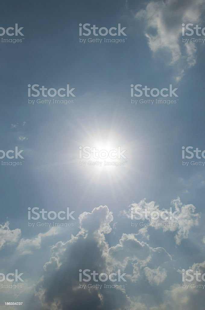 Fluffy beautiful clouds in the sky and shining sun royalty-free stock photo