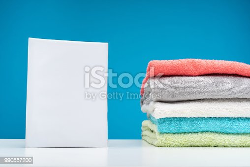 1146468307 istock photo Fluffy colorful towels and detergent on white board 990557200