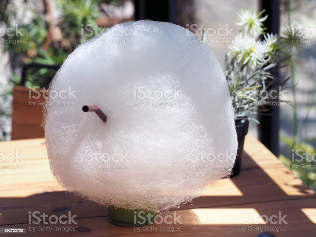 Fluffy cotton candy or candy floss over plastic glass of green tea latte with soft background. stock photo
