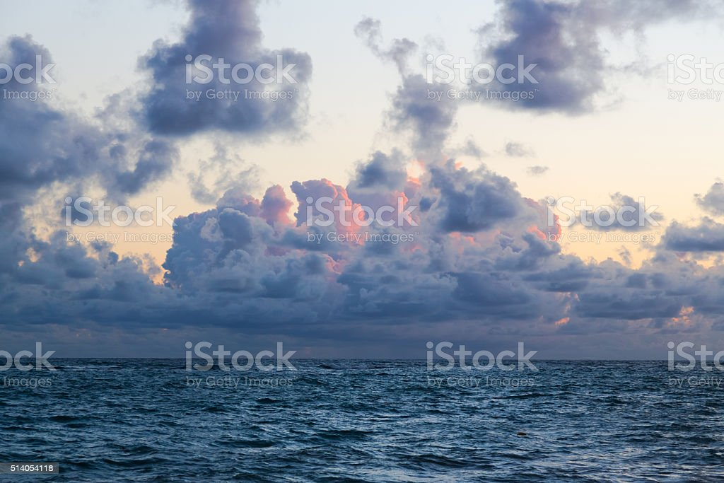 Fluffy dark clouds floating over turbulent ocean waters on sandy stock photo