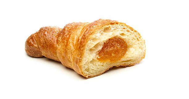 Fluffy French croissant with apricot jam filling stock photo