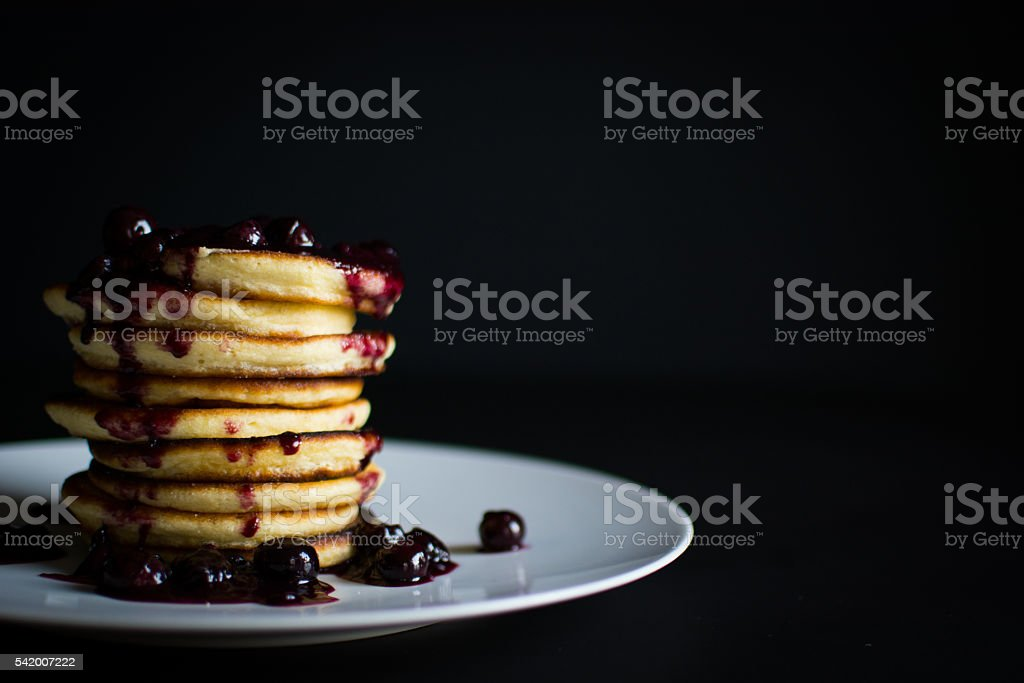Fluffy Pancake Stack with Blueberries on black background stock photo