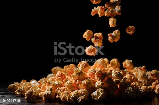 istock fluffy pieces of popcorn fall in slow motion against a black background 942941716