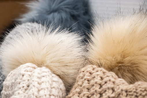 Fluffy pompon on a  knitted hat close-up.