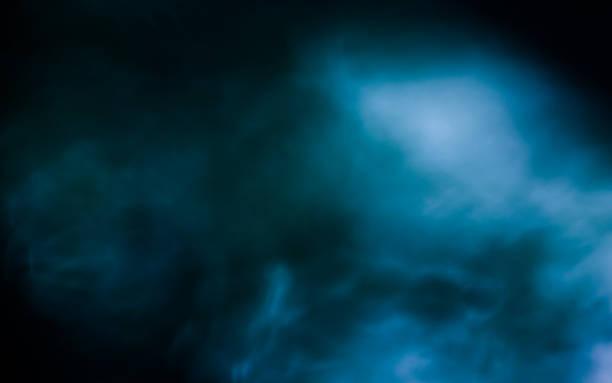 fluffy puffs of smoke and fog on black background - nebbia foto e immagini stock