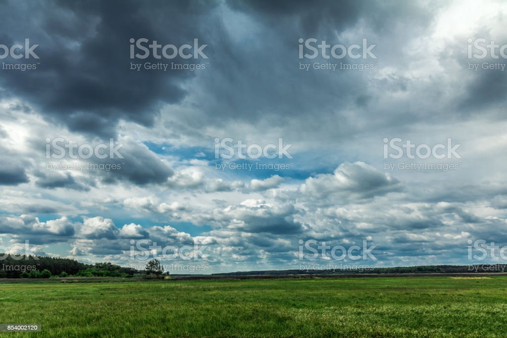 Fluffy rainy clouds over a green field in May royalty-free stock photo