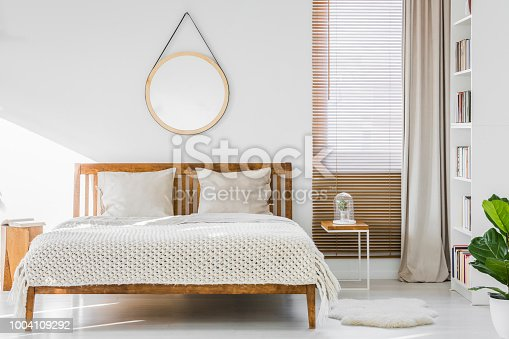 istock Fluffy rug placed next to double bed with white sheets and knit blanket standing in bright room interior with books on white rack, window with wooden blinds and empty round poster on the wall 1004109292