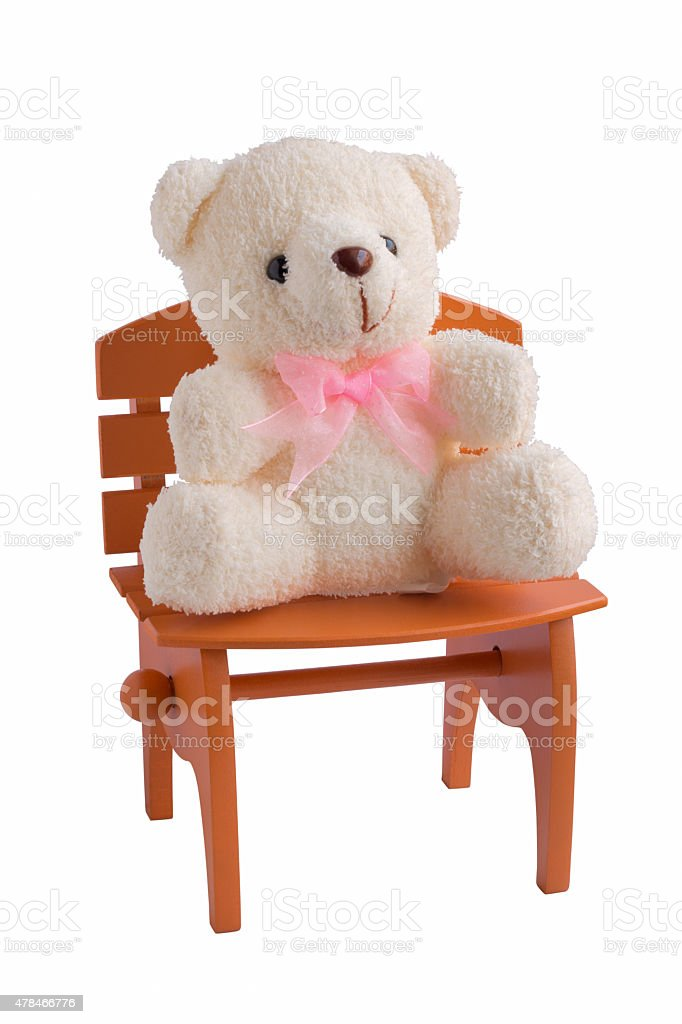 Fluffy teddy bear isolated on white background with brown chair.