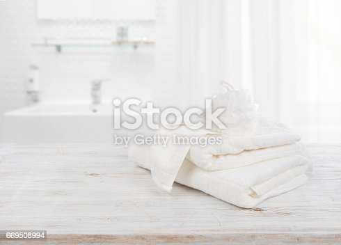 istock Fluffy towels and wisp of bast over blurred bathroom background 669508994
