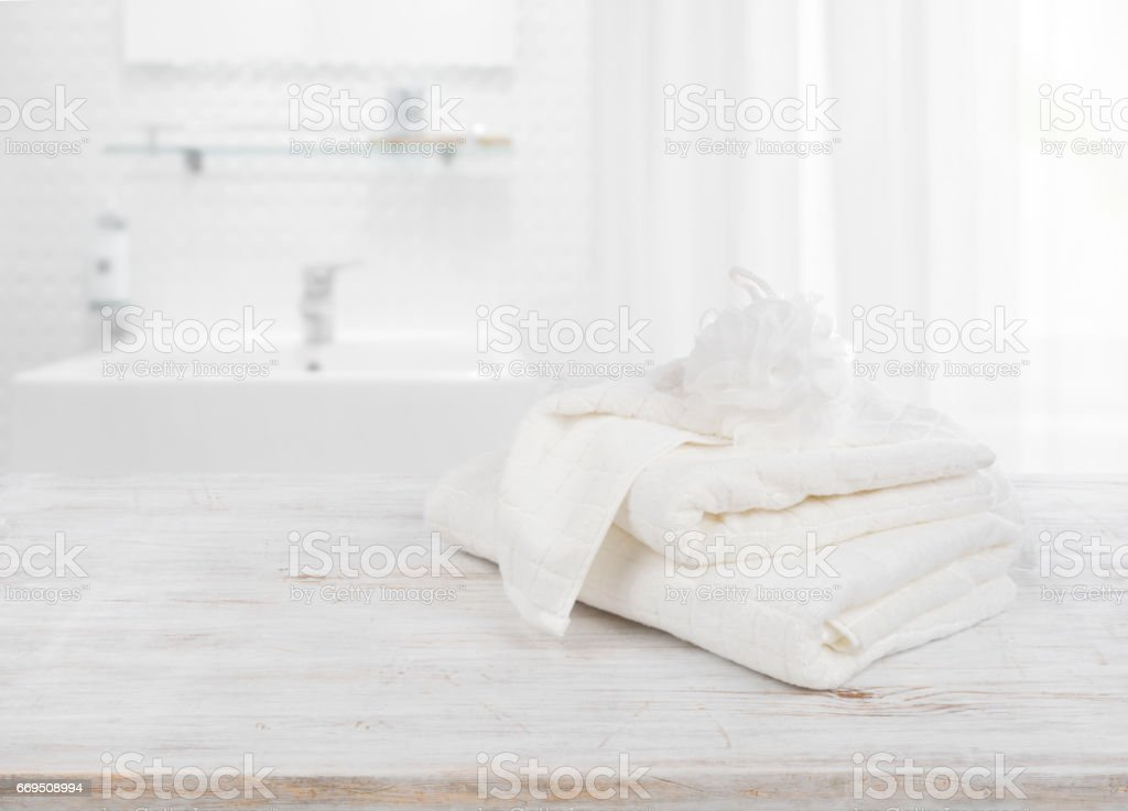 Fluffy towels and wisp of bast over blurred bathroom background - foto stock