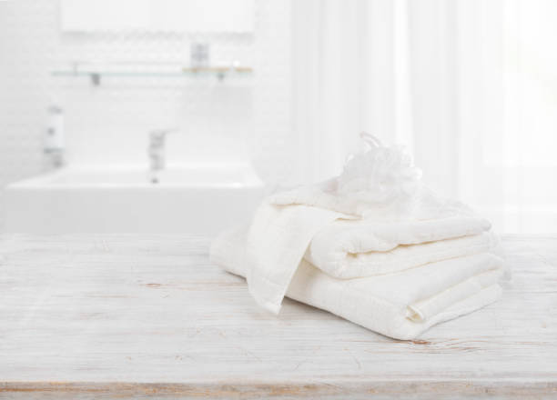 Fluffy Towels And Wisp Of Bast Over Blurred Bathroom Background Stock Photo