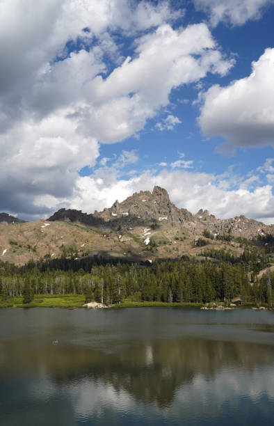 Fluffy, white clouds over a mountain lake in the summer. stock photo
