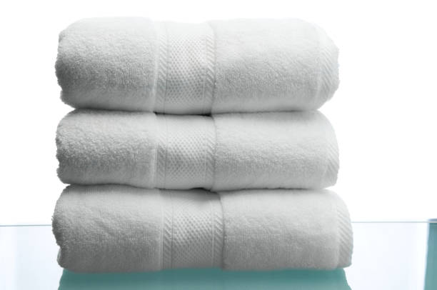 Fluffy White Towels on Reflective Surface stock photo