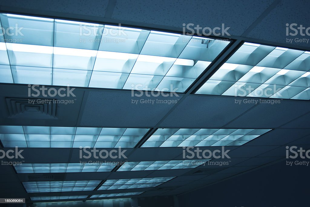Fluorescent lights and ceiling tiles in an office stock photo
