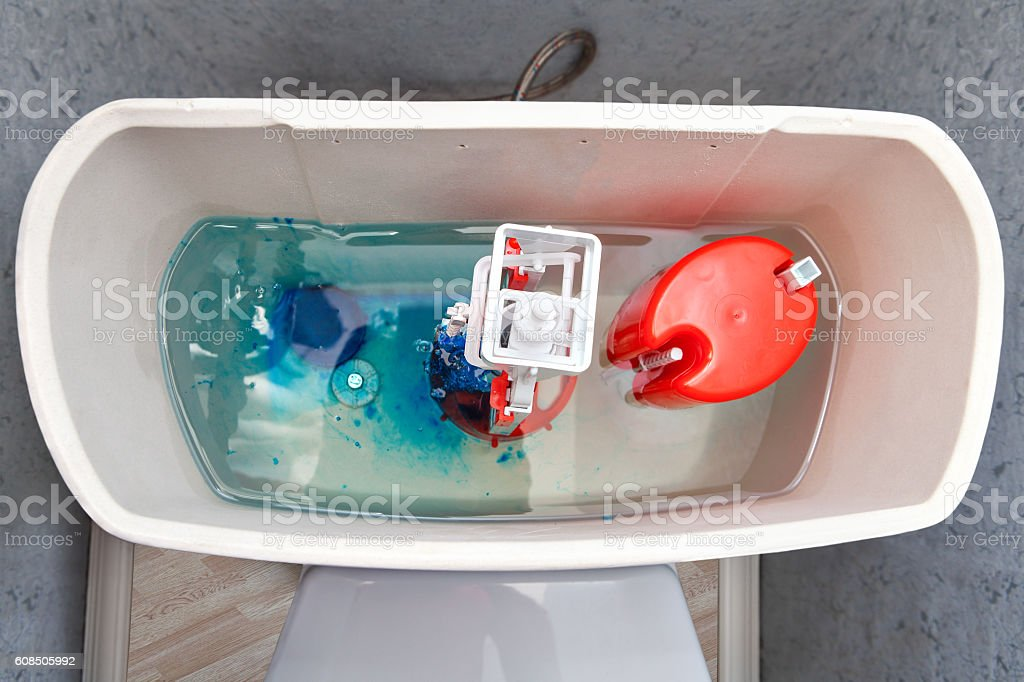 Flush mechanism inside cistern of toilet, blue water tablet diss stock photo