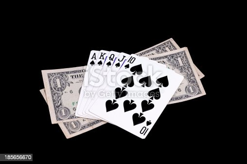 Flush royal cards with money isolated on black background